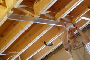 Checking for gaps in the new level frame of the ceiling with a 4-foot straight edge.