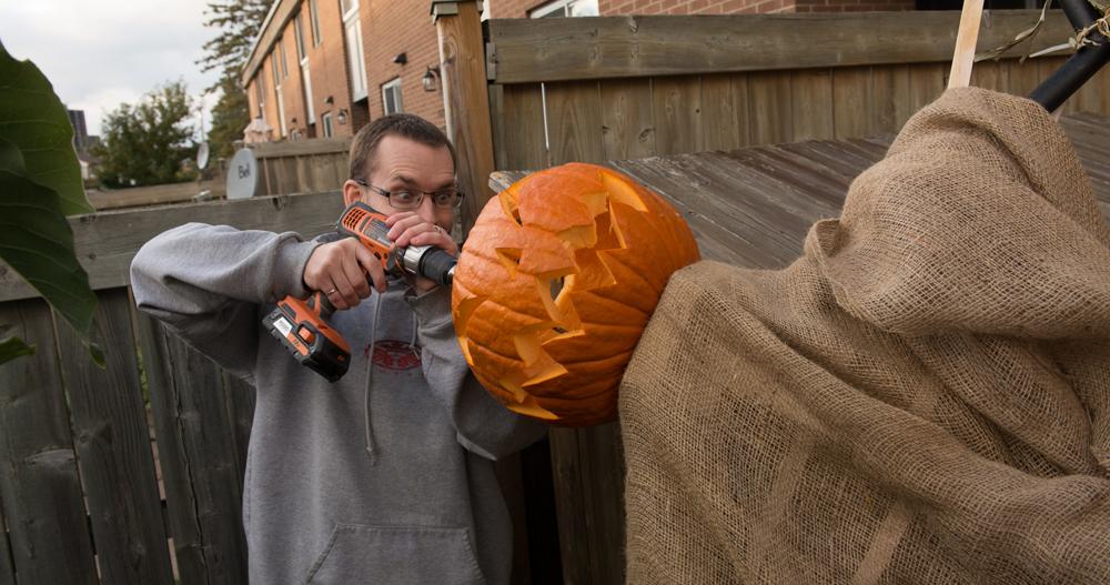 attaching pumpkin to stand pumpkin scarecrow drilling